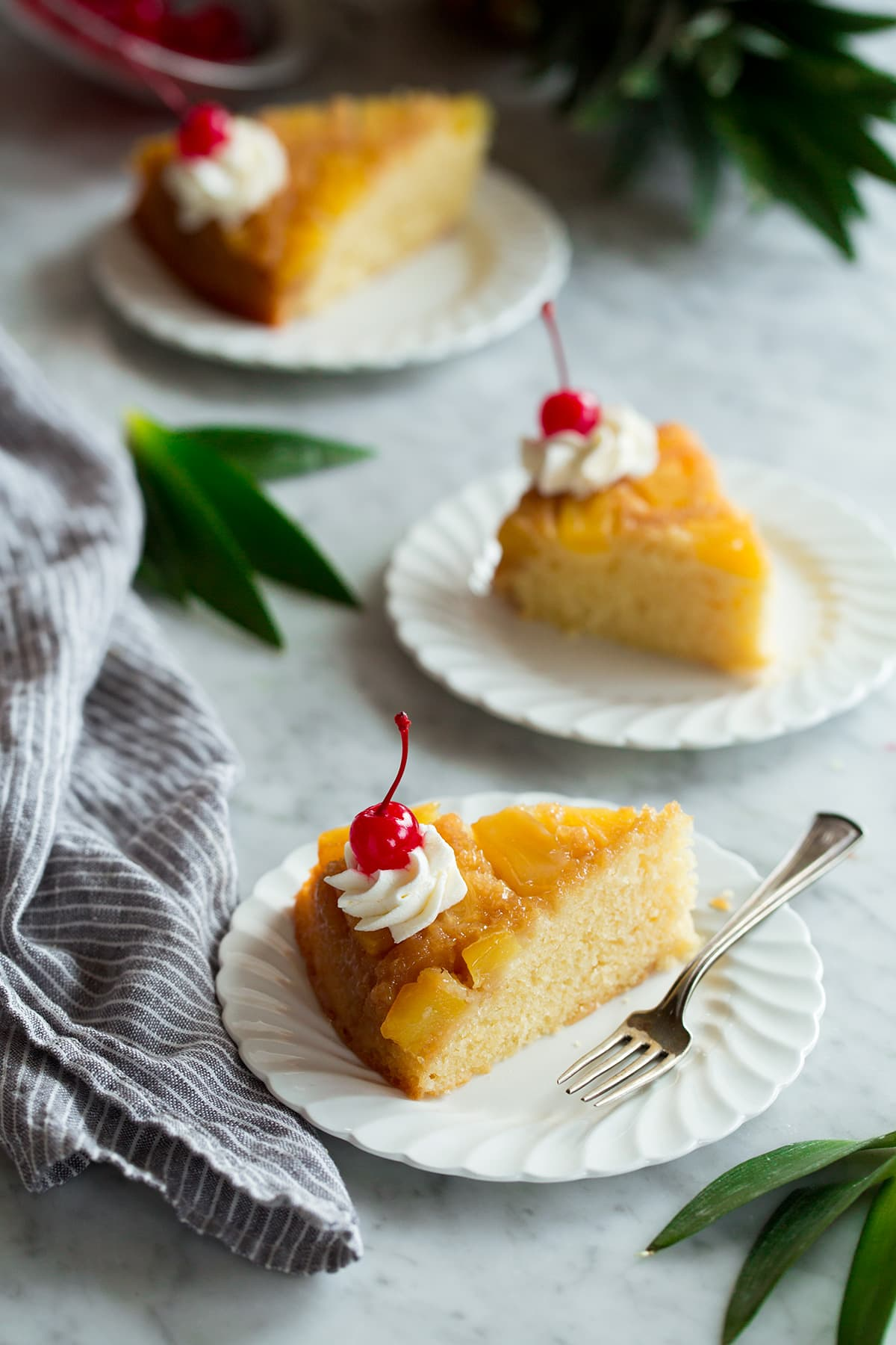 Three slices of Pineapple Upside Down Cake on individual white ruffled dessert plates.