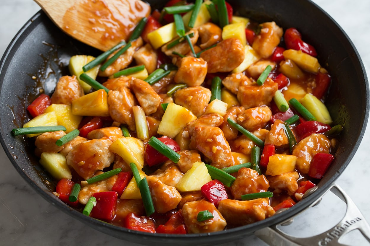 Cooking sauce with chicken, vegetables and pineapple in skillet to finish sweet and sour chicken.