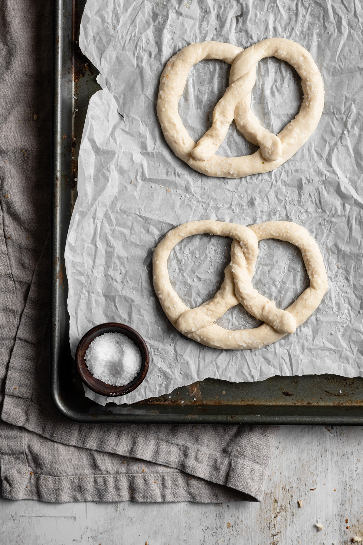 Image showing how to make soft pretzels. Shaping dough into pretzel shapes and they're placed on a parchment paper lined baking sheet to bake.