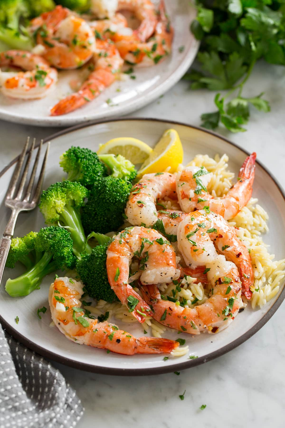 Baked shrimp on a white serving plate with orzo and broccoli.