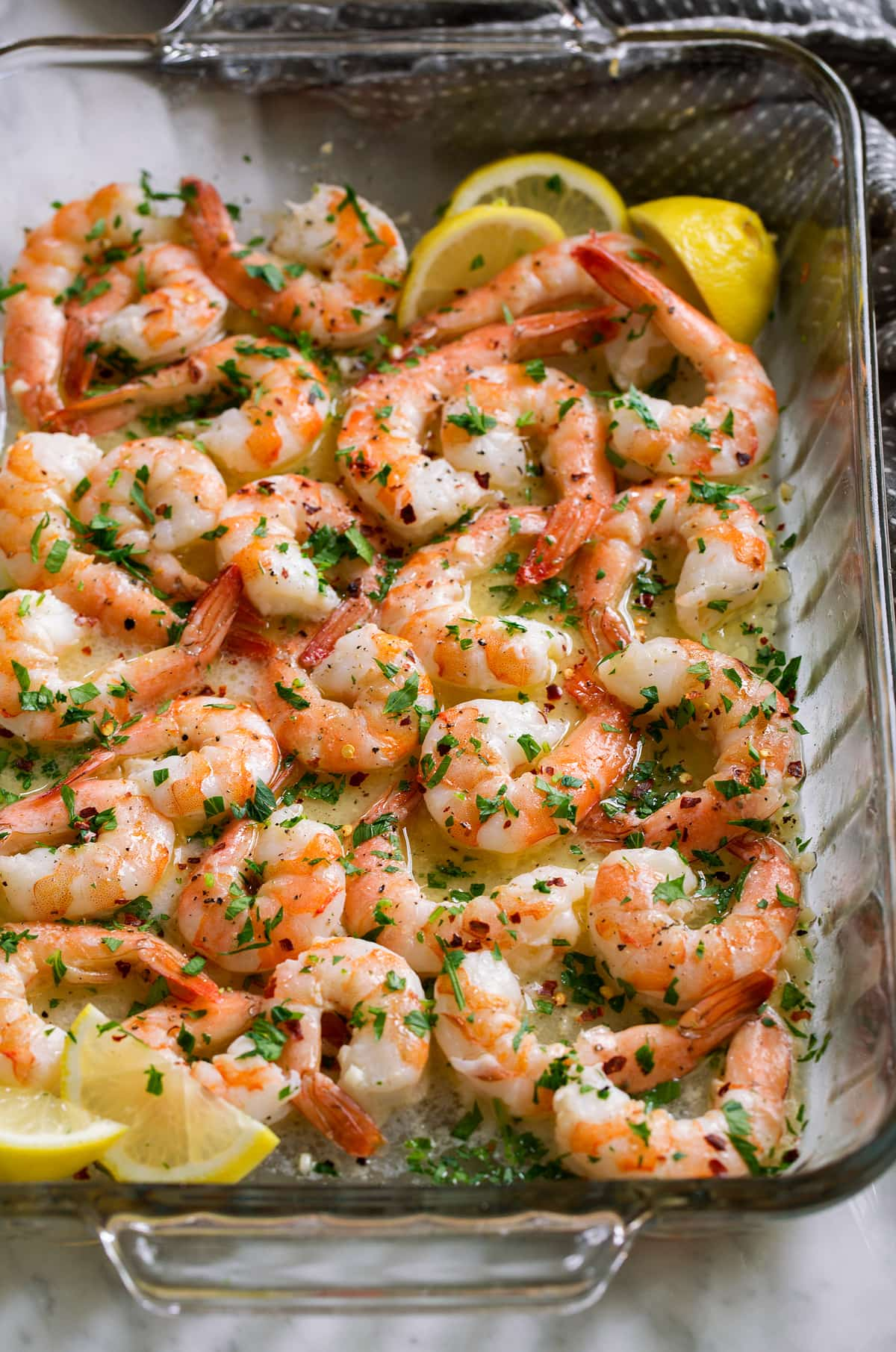 Glass baking dish filled with bake shrimp and garlic butter sauce, garnished with parsley and lemon wedges.