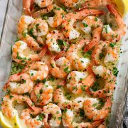 Overhead image of baked shrimp with lemon butter sauce in baking dish.