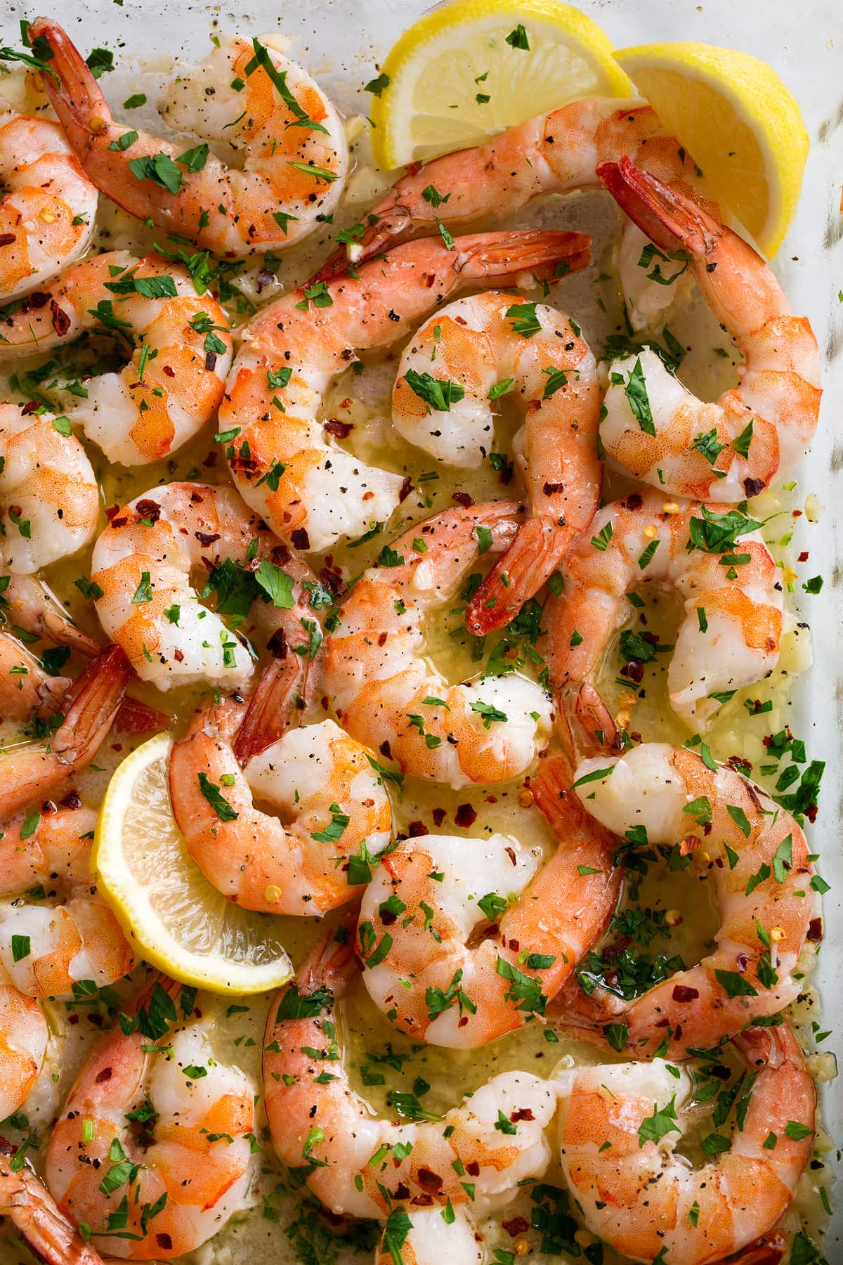 Close up image of baked shrimp in baking dish.