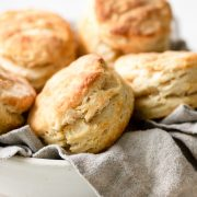 Tall and flaky biscuits stacked in a serving bowl with a grey kitchen cloth.