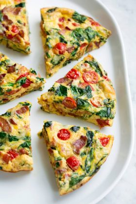 Six frittata wedges shown on a white serving platter set over a marble surface. Frittata is filled with bacon, spinach, tomatoes and swiss.
