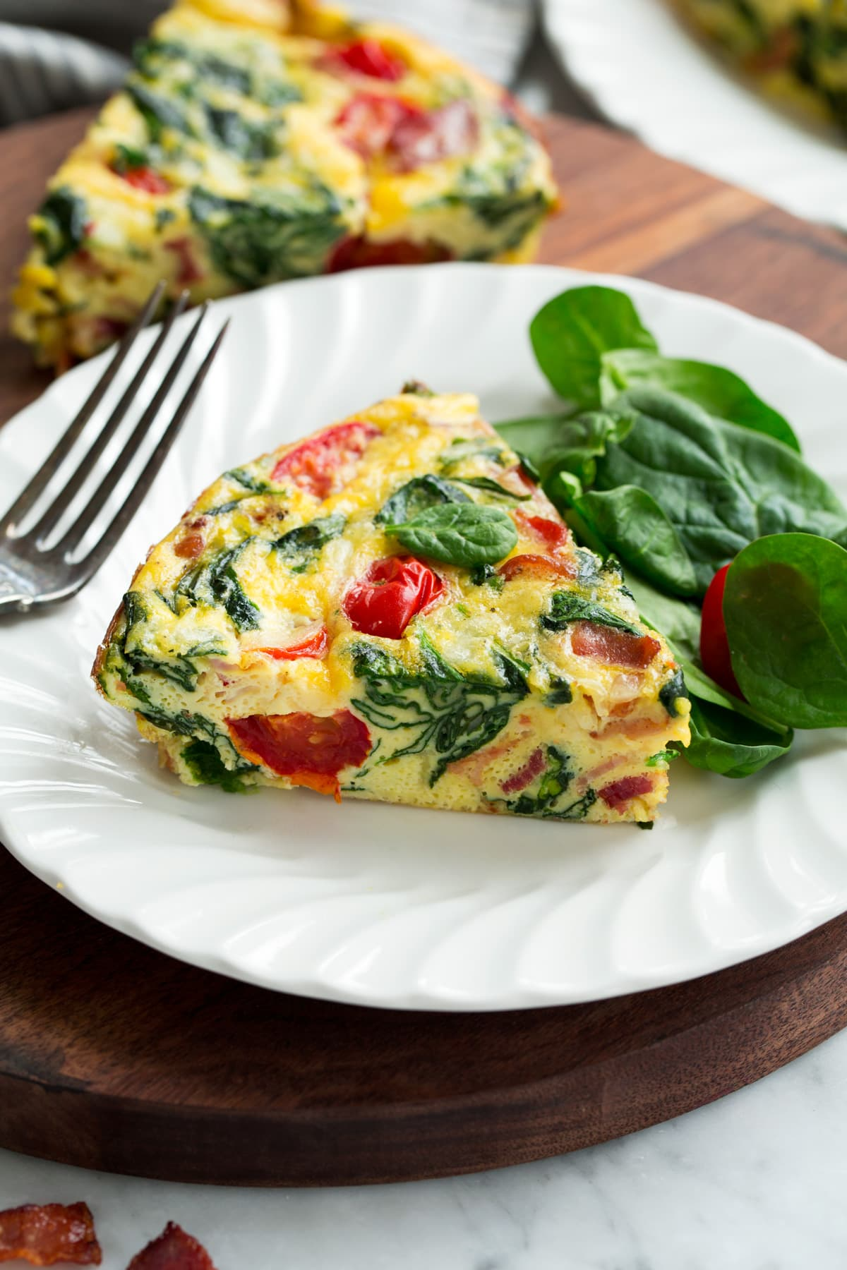 Single slice of frittata on a white serving plate.