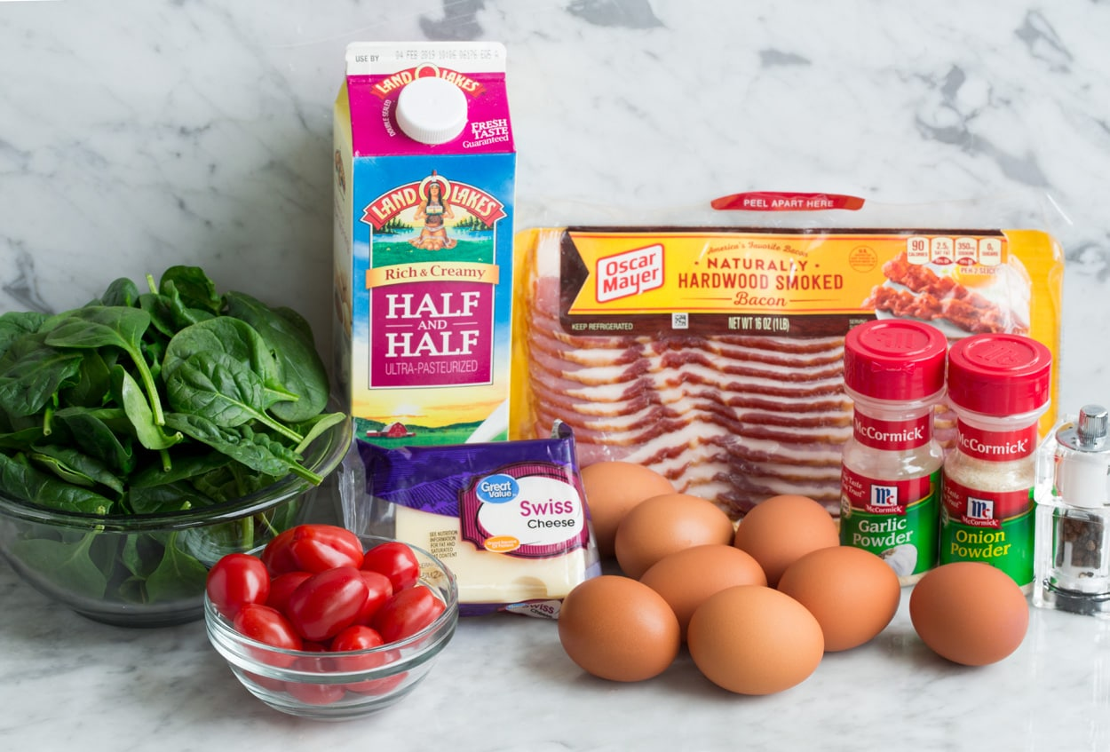 Ingredients needed to make a frittata shown here including eggs, bacon, swiss cheese, spinach, tomatoes, half and half, garlic powder, onion powder, salt and pepper.