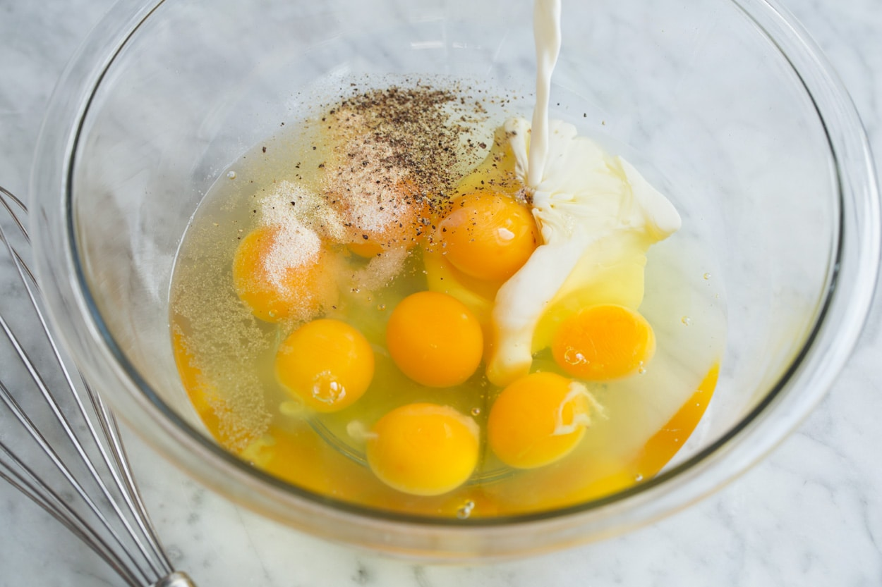 Showing how to make a frittata, mixing eggs, spices and half and half in a glass mixing bowl.