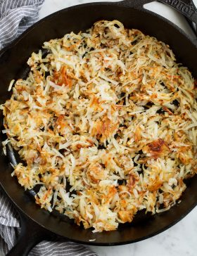 Overhead image of shredded hash browns in black cast iron skillet.