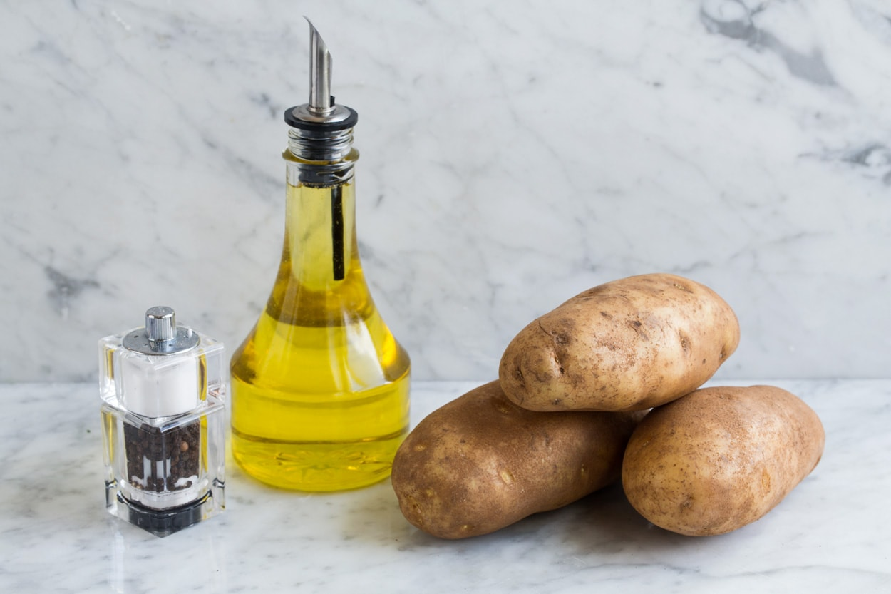 Ingredients needed to make hash browns shown here including russet potatoes, olive oil, salt and pepper.