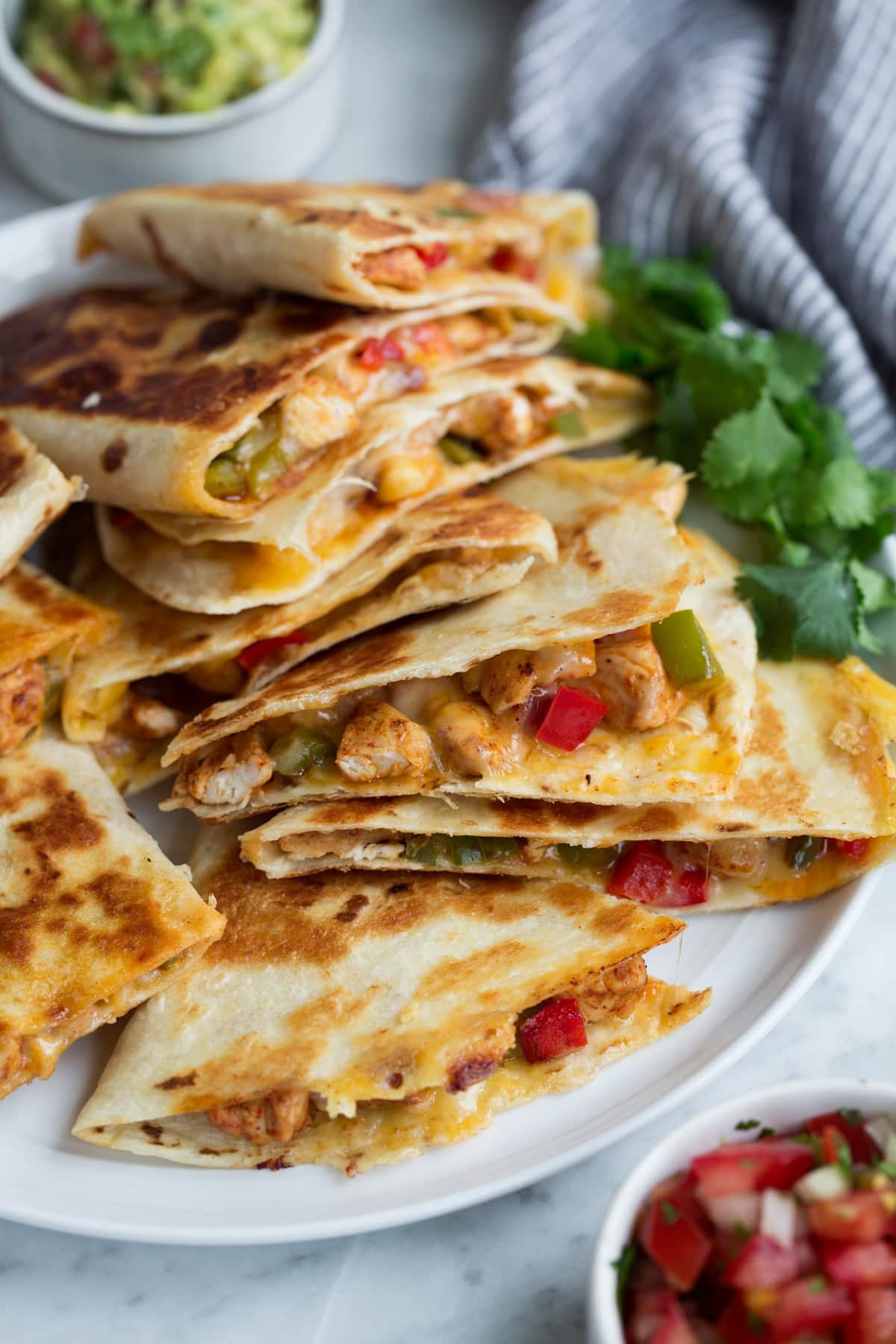 Quesadillas on a plate served with guacamole and salsa.
