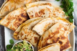 Overhead image of 8 quesadilla wedges on a white oblong platter served with pico and guacamole.