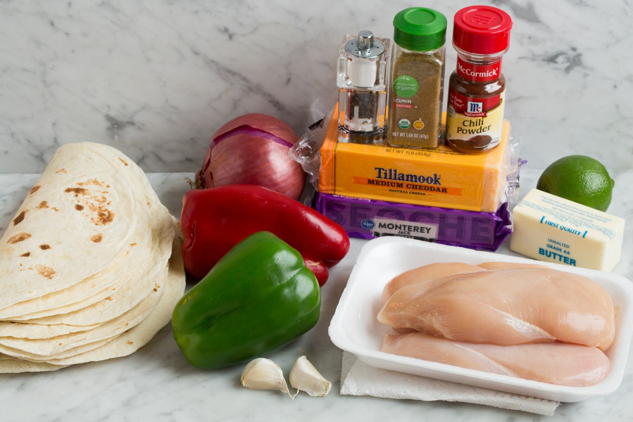 Quesadilla ingredients shown here including tortillas, butter, cheese, chicken, bell peppers, red onion, garlic, cumin, chili powder and lime.