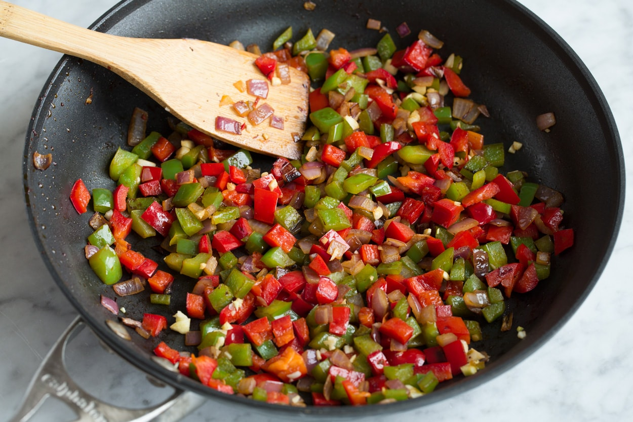 Sauteing bell peppers and onions in skillet to use as a filling for quesadillas.