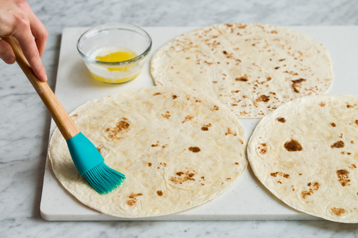 Brushing tortillas with melted butter to make quesadillas.