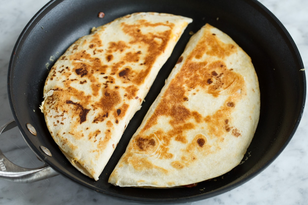 Two quesadillas in a skillet shown after cooking with golden brown exterior.