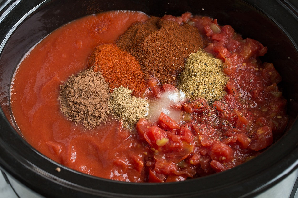 Adding tomatoes, tomato sauce, and spices to slow cooker for chili.