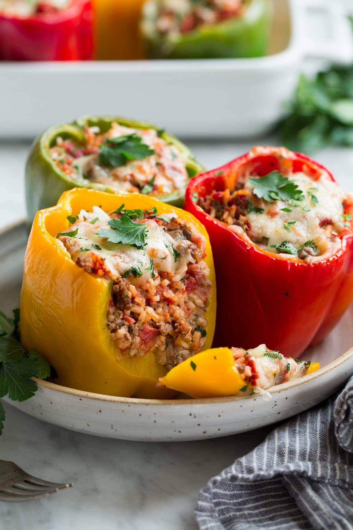 Red yellow and green stuffed pepper in a serving bowl.