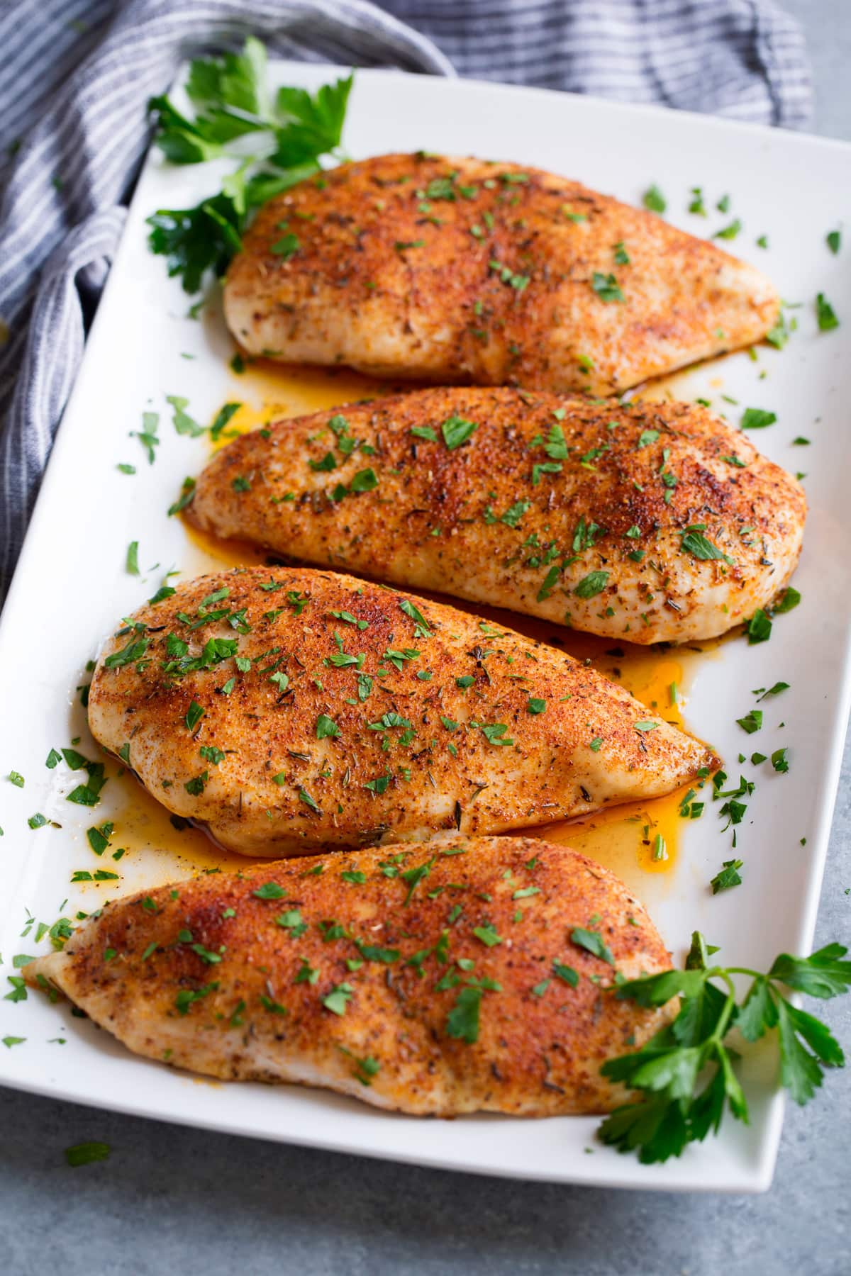 Four seasoned baked chicken breasts on a white rectangular serving platter garnished with parsley.