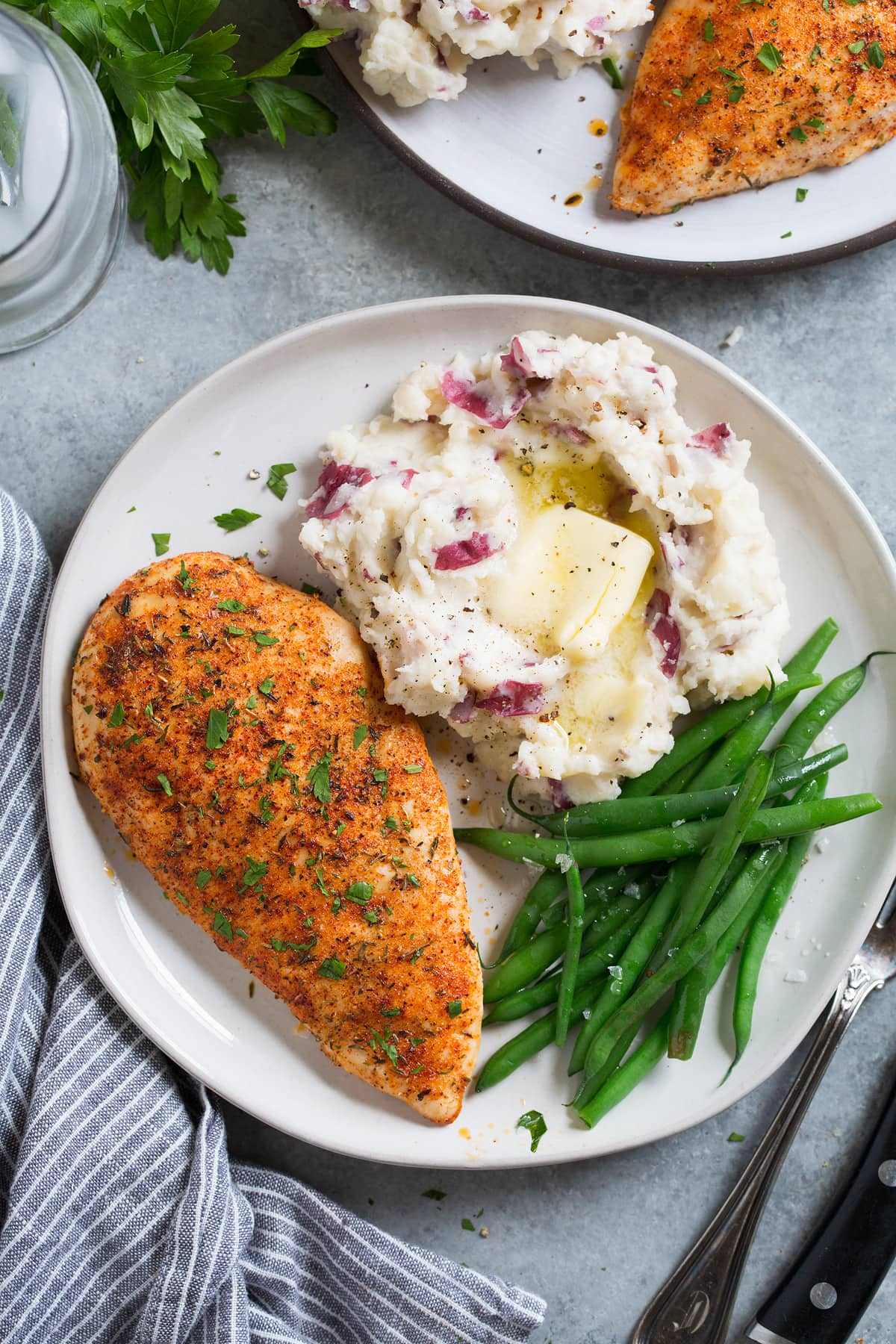 Overhead image of a seasoned baked chicken breast on a white serving plate along with a side of mashed potatoes and steamed green beans.