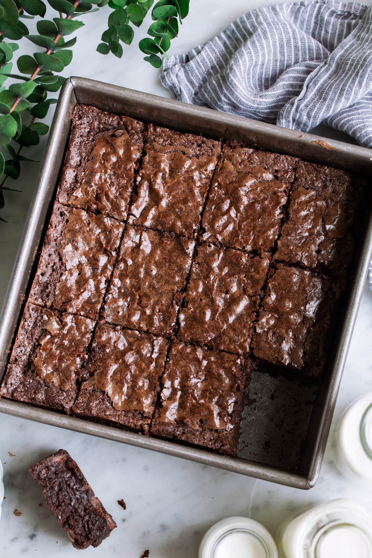 Overhead image of cut brownie squares in a square baking dish.