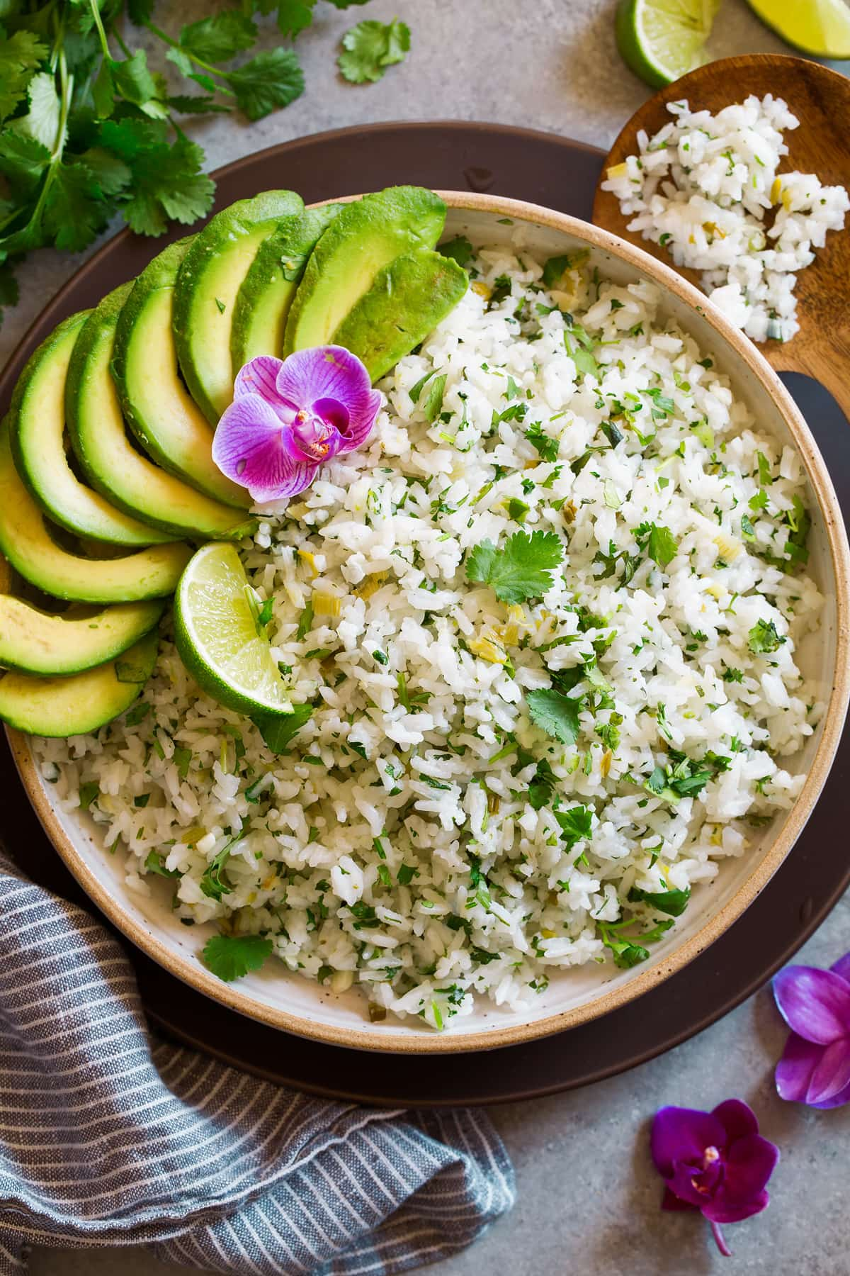 Cilantro Lime Rice in a cream ceramic serving bowl set over a brown matte plate. Rice is garnished with cilantro, lime, avocado and orchid flower.