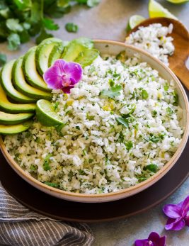 Serving bowl full of cilantro lime rice garnished with avocado slices, cilantro leaves, orchid flower and lime.
