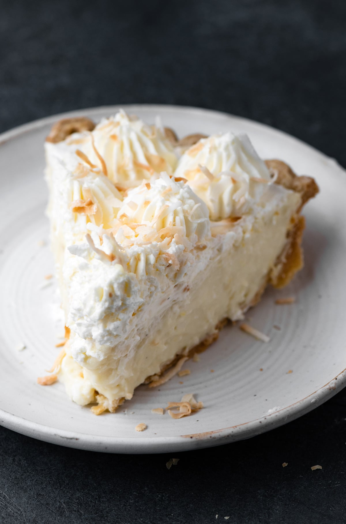 Single slice of coconut cream pie made from scratch on a white dessert plate.