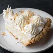 Single slice of coconut cream pie on a white dessert plate.