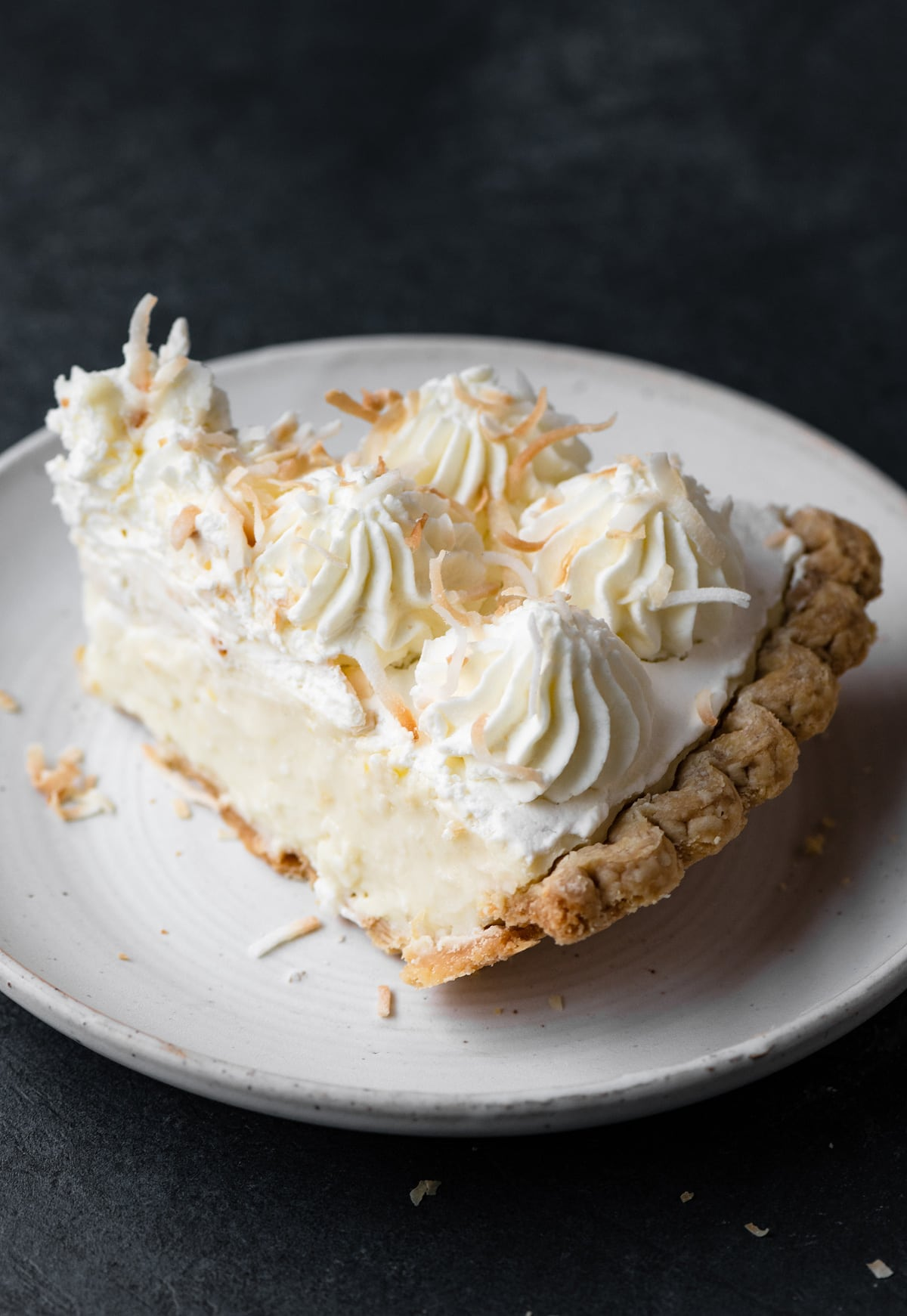 Slice of coconut cream pie on a white plate set over a dark grey tabletop.