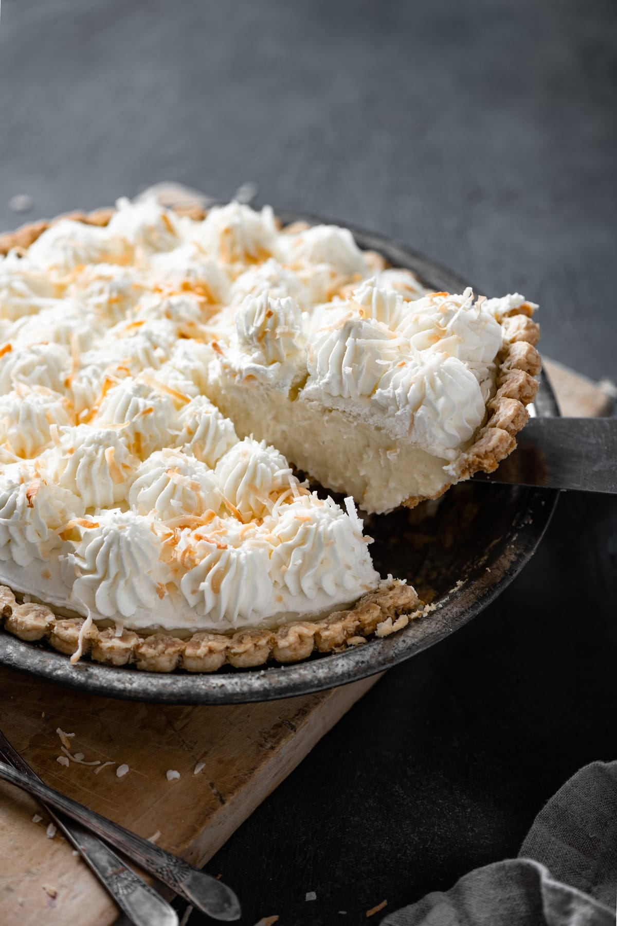 Removing a slice of coconut cream pie from the whole coconut cream pie in pie dish.