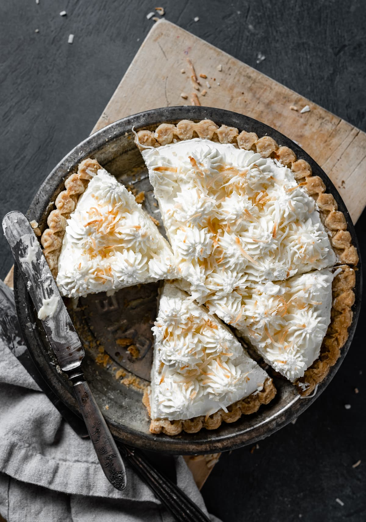 Whole coconut cream pie in a pie dish with slices cut. Pie is sitting on a wooden cutting board over a dark surface.