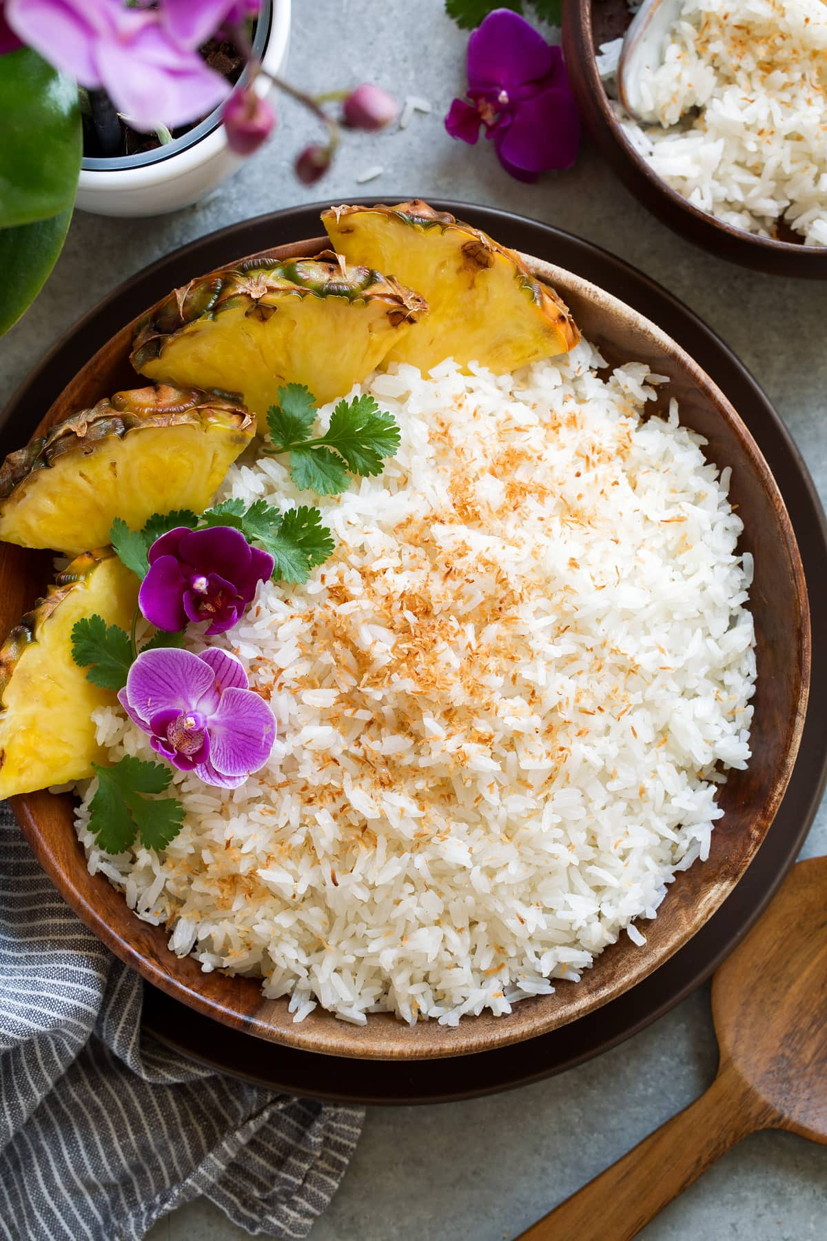 Wooden bowl full of Coconut Rice topped with flowers, cilantro and a side of fresh pineapple.