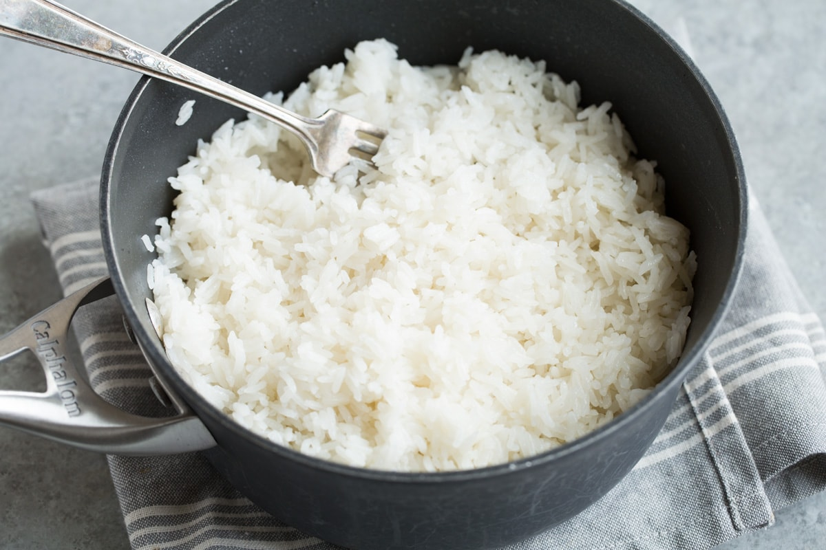 Fluffing finished coconut rice in saucepan with a fork.