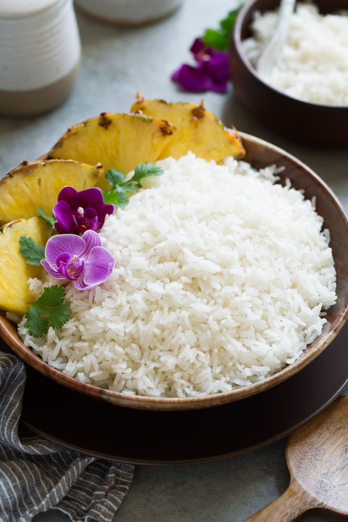 Coconut rice in a wooden serving bowl garnished with orchids, cilantro and pineapple wedges on the side.