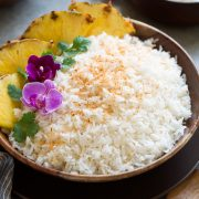 Coconut rice in a wooden bowl set over a brown plate on a grey surface.