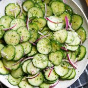 Cucumber Salad in white serving bowl set over a dark grey napkin.
