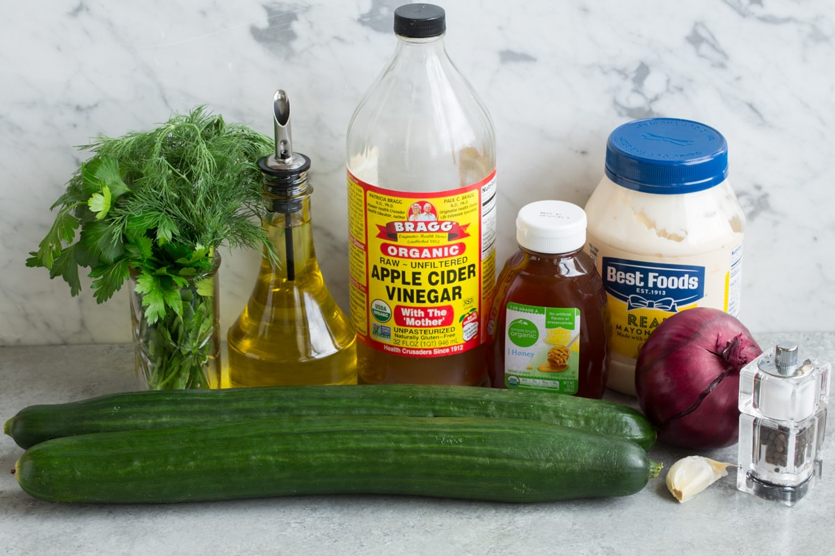 Ingredients needed to make cucumber salad shown here including English cucumbers, mayonnaise, olive oil, garlic, apple cider vinegar, dill, parsley, honey, and red onion.