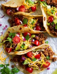 Row of ground beef tacos on parchment paper.