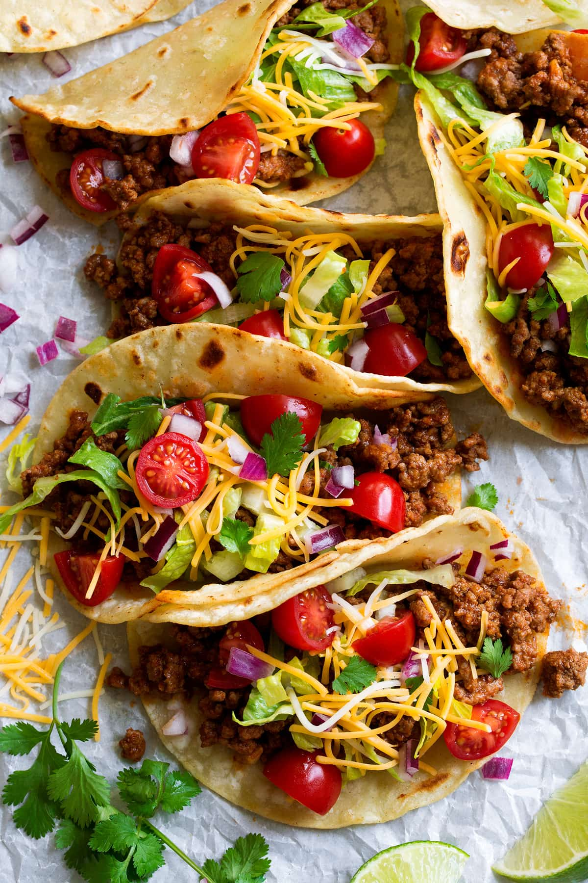 Row of tacos filled with ground beef filling, cheese, lettuce, tomatoes, and cilantro.