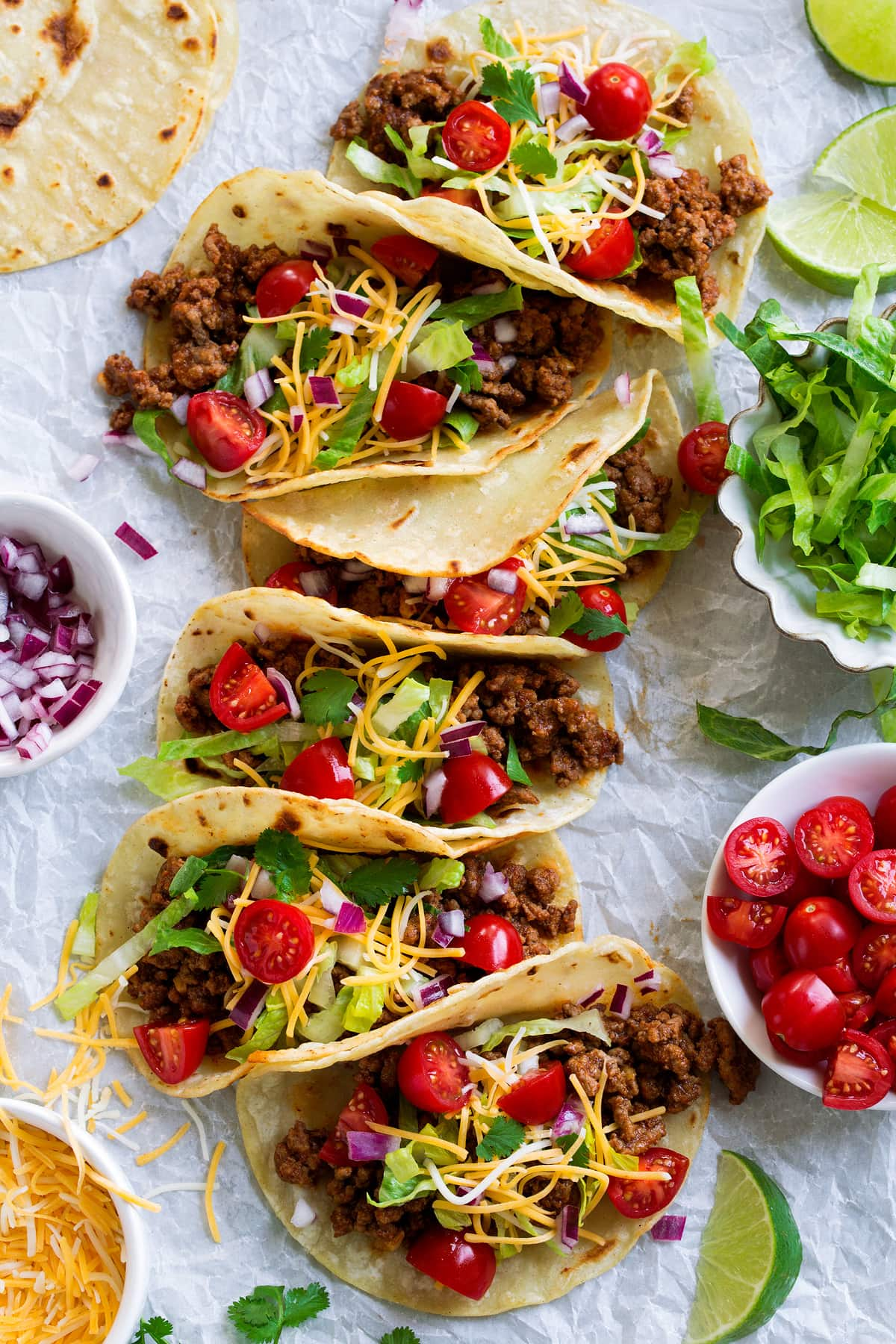 Long row of ground beef tacos on parchment paper finished with fresh toppings.