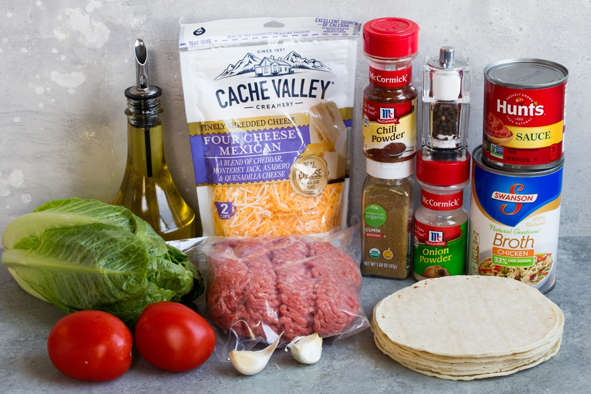 Ingredients needed to make tacos shown here including ground beef, oil, spices, tomato sauce, beef broth, tortillas, cheese, lettuce, garlic tomatoes.