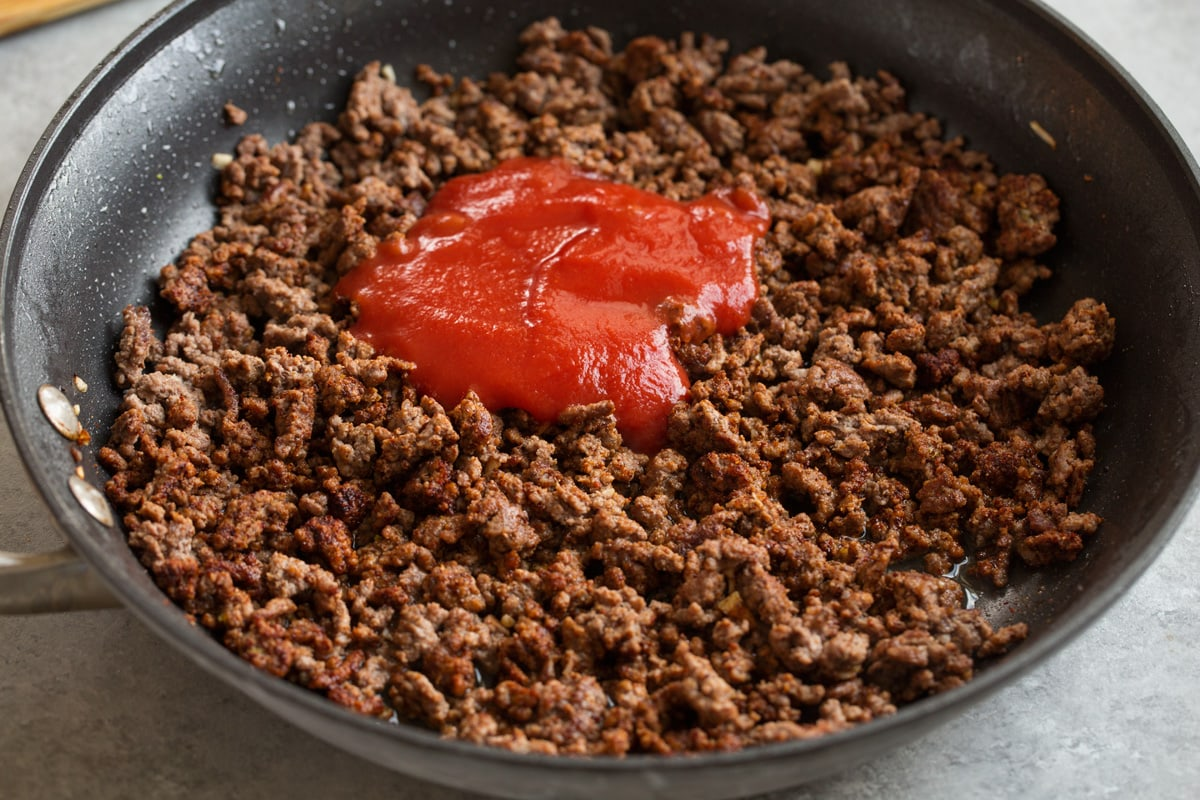 Adding tomato sauce and chicken broth to taco meat filling in skillet.