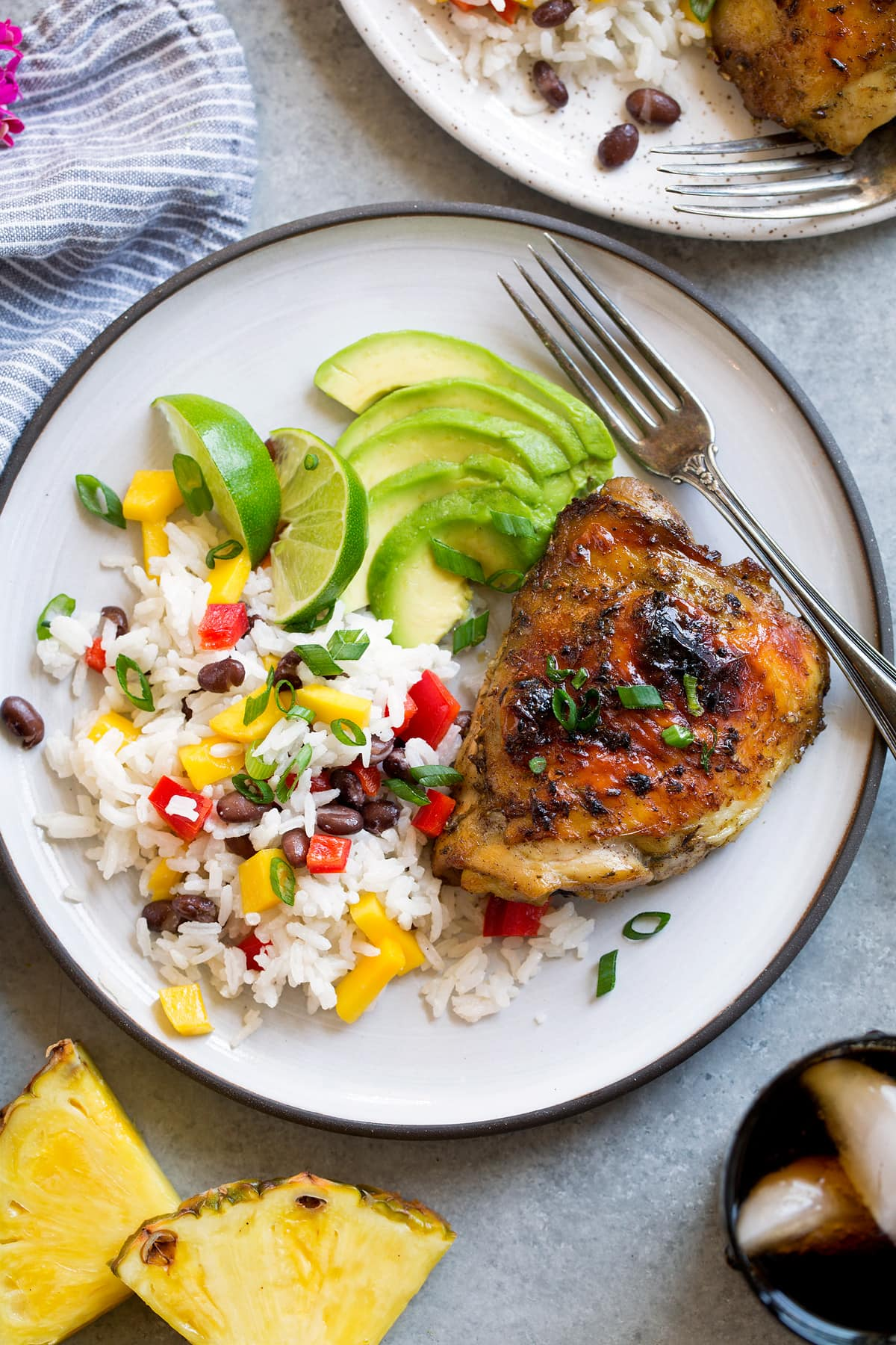 Single piece of jerk chicken with a side of coconut rice and avocado.