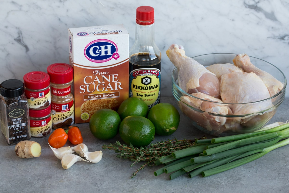 Jerk Chicken ingredients shown here including chicken pieces, green onions, thyme, limes, soy sauce, brown sugar, cinnamon, allspice, nutmeg, pepper, scotch bonnet pepper, garlic, and fresh ginger.