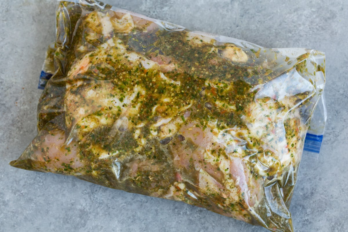 Soaking chicken pieces in a resealable bag with marinade.