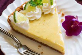 Slice of Best Key Lime Pie on white scalloped dessert plate set over a maroon napkin.