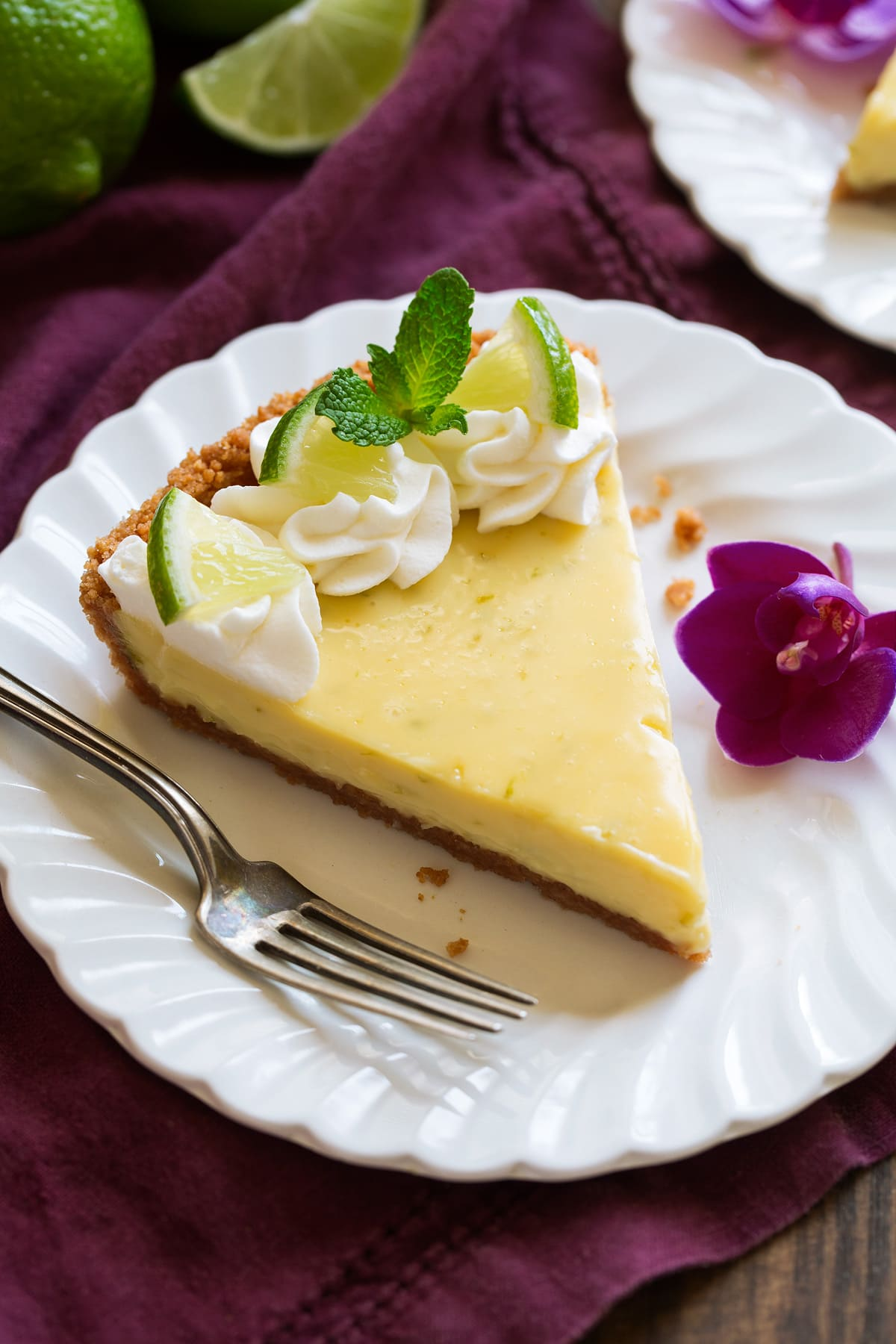 Slice of Best Key Lime Pie on white scalloped dessert plate set over a maroon napkin.