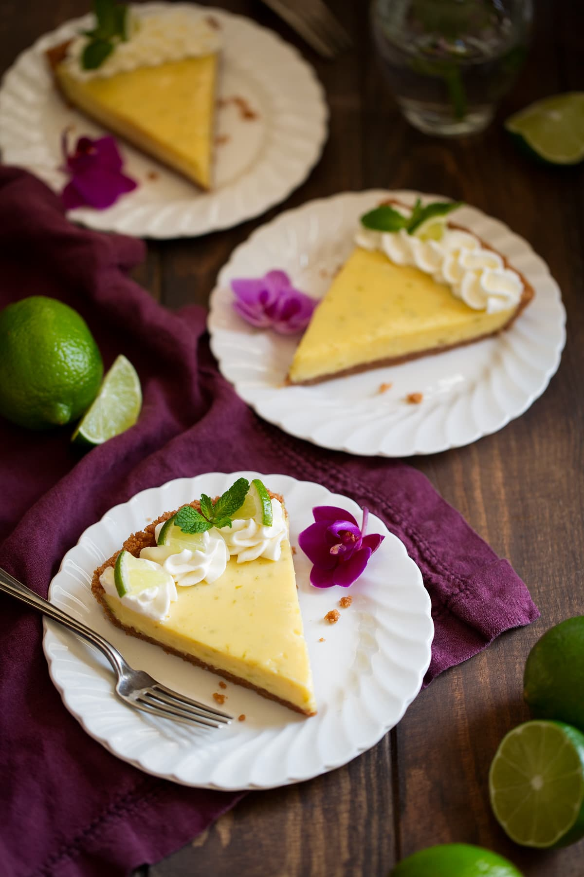 Three slices of key lime pie on white scalloped dessert plates set over a maroon linen napkin. Plates are decorated with purple orchids.