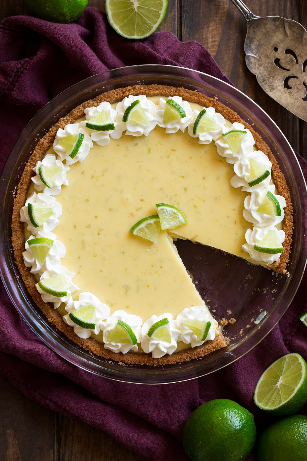 Whole key lime pie with one slice removed. Pie is decorated with swirls of whipped cream around the edges and mini lime slices.